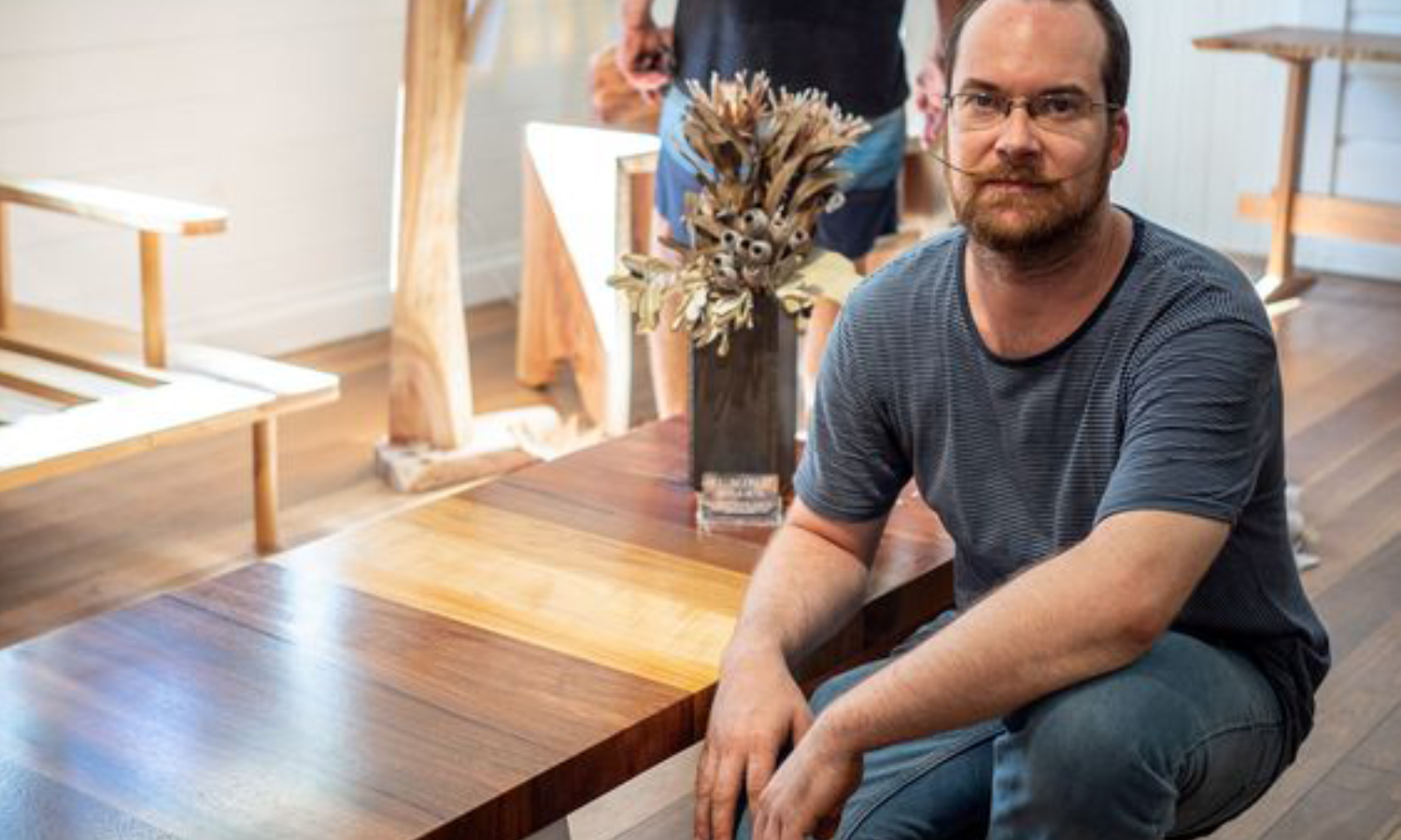 Laurent with his mixed timber coffee table. Image courtesy of QTT